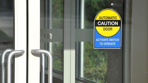 Puerta de vidrio con una señal que dice que es automática