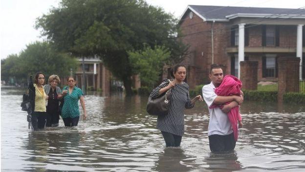 Familias caminan en las calles inundadas