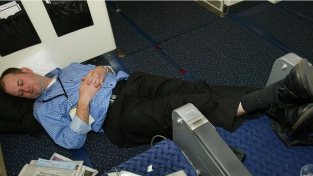 A passenger asleep in the aisle of an airplane