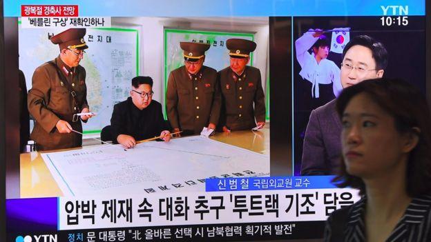 Una mujer pasa en Seúl junto a una pantalla de televisión con la imagen de Kim Jong-un
