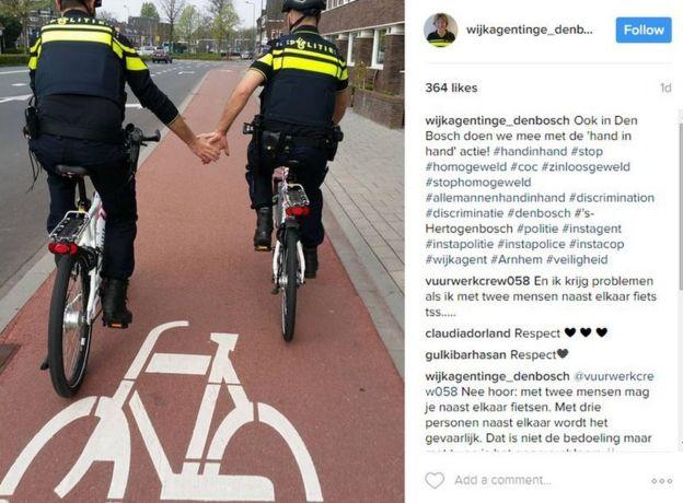 Un post de Instagram que muestra a dos policías montados en bicicletas tomándose de la mano.