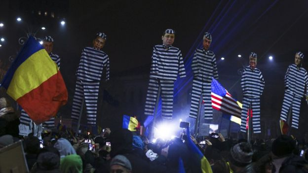 Romanian protesters hold up effigies of government officials
