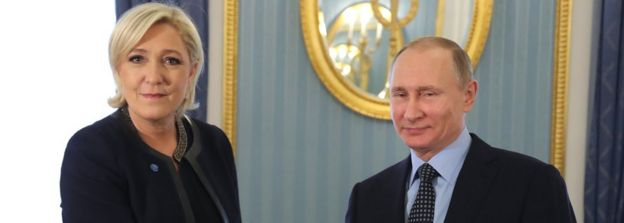 French presidential candidate and far-right Front National political partys leader Marine Le Pen (L) shakes hands with Russian President Vladimir Putin (R)