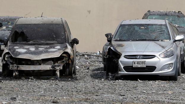 Carros dañados cerca del edificio donde ocurrió el incendio en la madrugada del viernes.