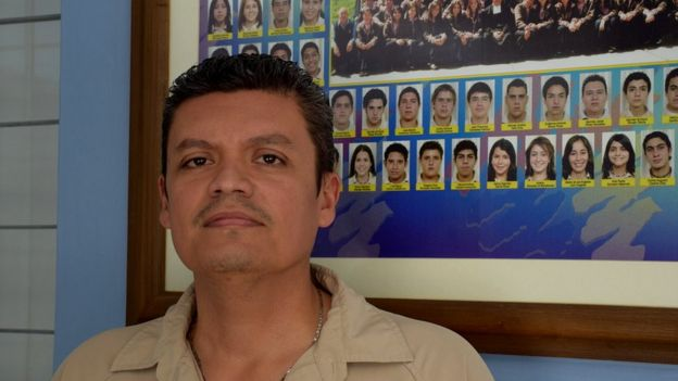 Javier Ramírez in front of a framed photo showing school graduates