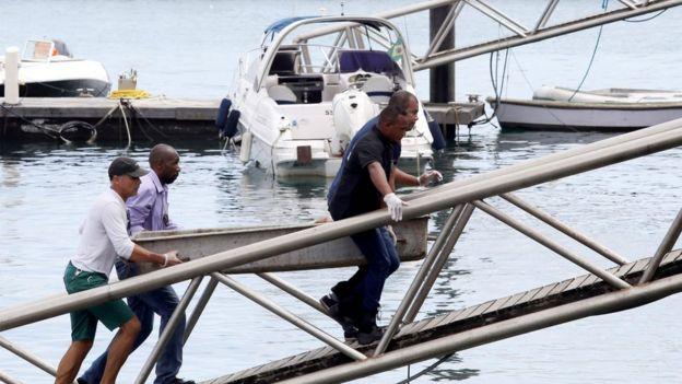 Rescatistas llevan el cuerpo de una víctima a un barco de la Marina de Brasil.