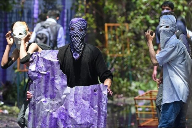 Kashmiri students wearing face masks look towards Indian government forces during clashes in central Srinagar