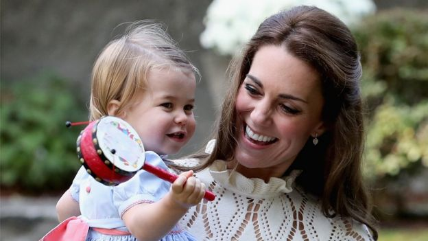 Princess Charlotte playing with a toy in Kate's arms