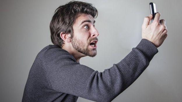 Un hombre mira a su teléfono enojado