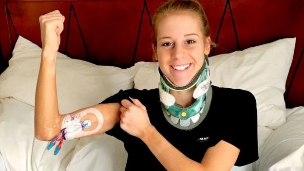 Victoria Graham in a hospital bed, showing her IV line and in a head brace.