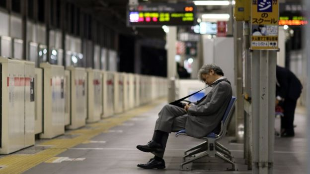 A man asleep in a subway station in Tokyo.