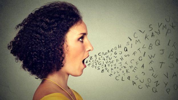 Salen letras de una mujer de perfil con la boca abierta