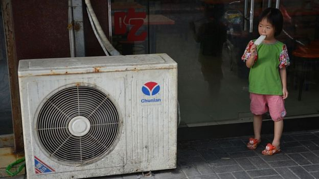 A young girl eats an ice lolly next to an air conditioning unit in Shanghai