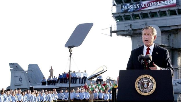 George W Bush with the banner on the aircraft carrier USS Abraham Lincoln in May 2003