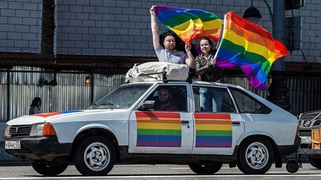 Unos jóvenes con la bandera gay en un coche
