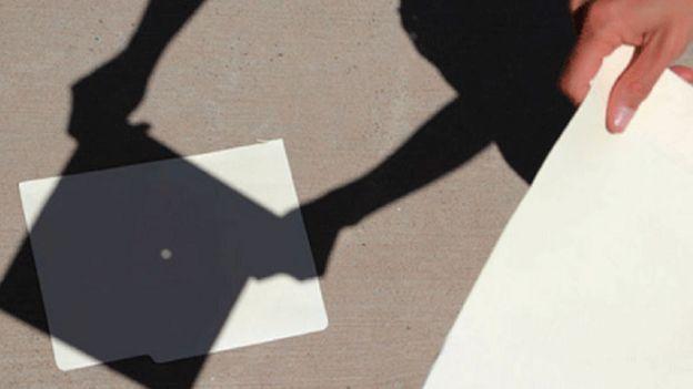 Lámina con un agujerito para ver la proyección del eclipse