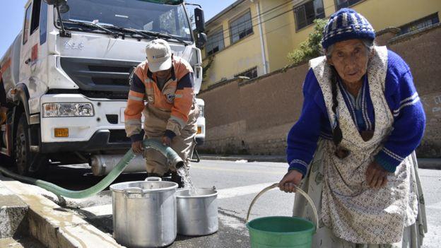 Mujer en Bolivia cargando agua de una cisterna en un balde en Bolivia