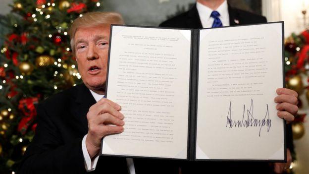 Presiden Trump memperlihatkan dokumen pengakuan Yerusalem sebagai ibu kota Israe yang sudah ditandatanganinya.