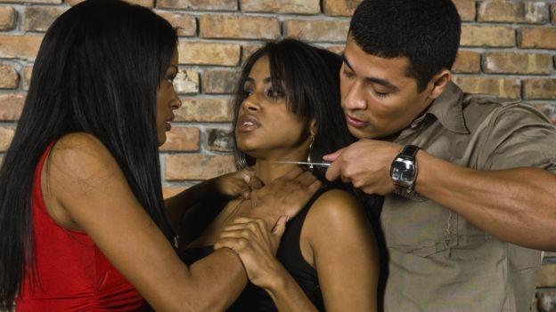 Mujer y hombre amenazando a otra mujer.