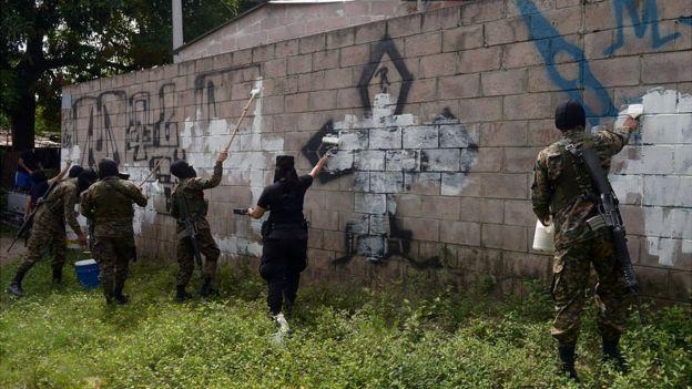Militares tapan con pintura graffitis de la Mara Salvatrucha.