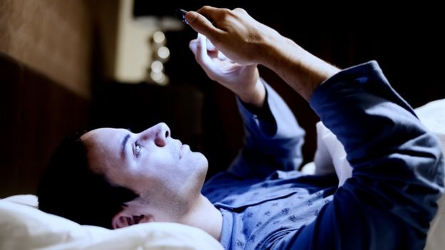 A young man looks at his cell phone in bed.