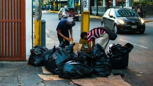 Dos hombres buscan comida en la basura en Caracas.