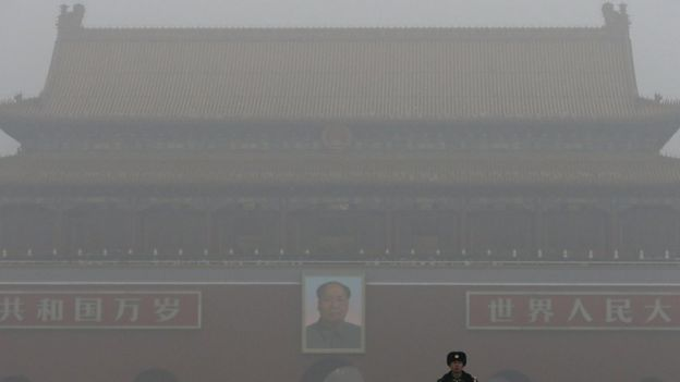 A paramilitary police officer stands guard near Tiananmen Gate shrouded with heavy pollution and fog in Beijing, China on Tuesday, Dec. 1, 2015.