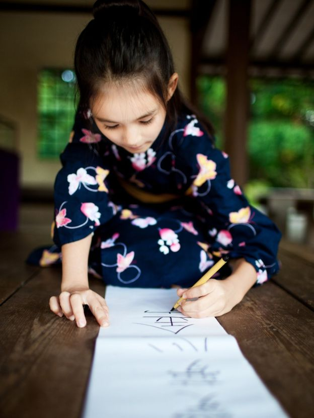 niña escribe en un papel