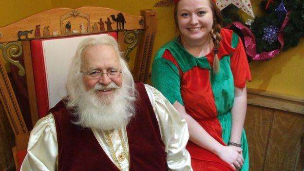 Santa Claus con una de sus ayudantes