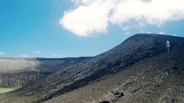 Un uomo in piedi sul terreno vulcanico dell'isola.  (Foto: Gianpiero Orbassano)