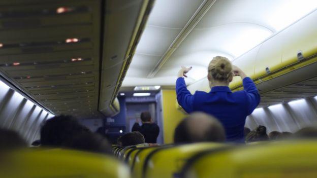 Comissária de bordo orienta sobre saídas de emergência