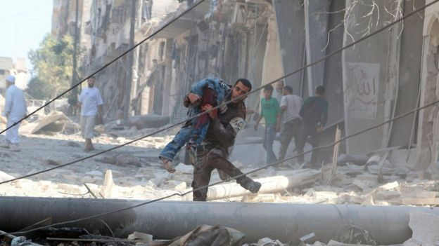 A man carries an injured man amid rubble of damaged buildings after an airstrike on Aleppo's rebel held al-Fardous district, Syria 16 July 2016.