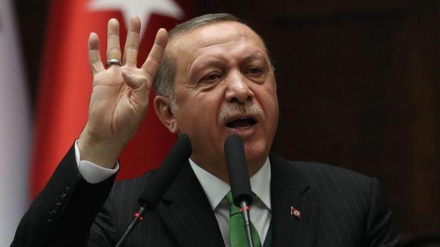President Erdogan raises a hand during a speech last week