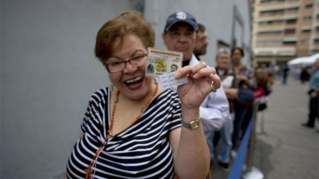 A woman shows her identification card before entering to validate her signature at the Venezuelan National Electoral Council, CNE, headquarters in Caracas, Venezuela, Monday, June 20, 2016.