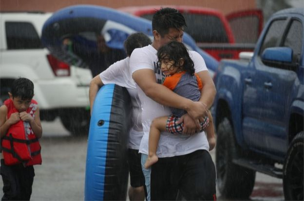 Mario Qua holds Wilson Qua as they evacuate their flooded home after the area was inundated with flooding from Hurricane Harvey on 27 August 2017 in Houston, Texas