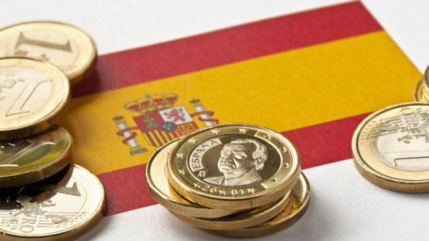 Monedas de euro sobre una bandera española.