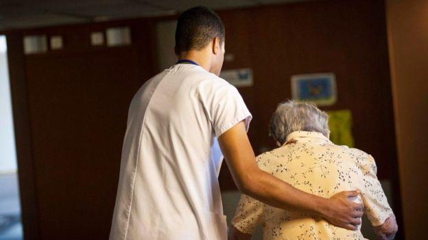 Un enfermero ayudando a caminar a una anciana