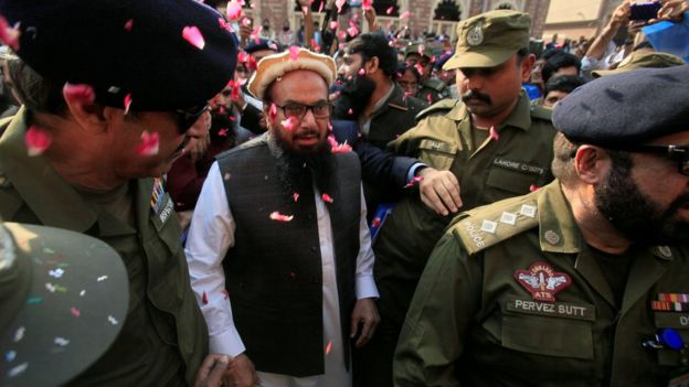 Hafiz Saeed is showered with flower petals as he walks to court before a Pakistani court ordered his release from house arrest in Lahore