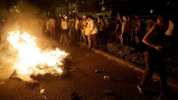 Manifestantes en Guayaquil encienden fuego en una calle.