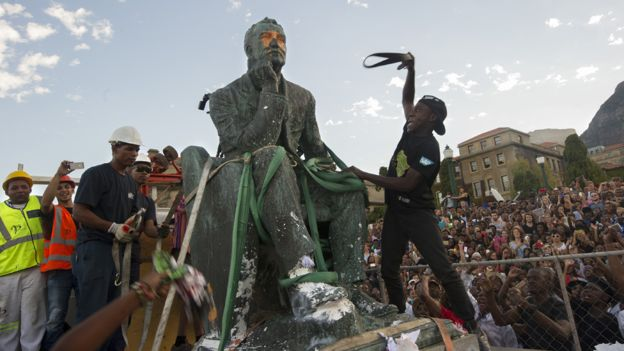Students attack the defaced statue of British mining magnate and politician, Cecil John Rhodes, as it is removed by a crane from its position at the University of Cape Town on April 9, 2015