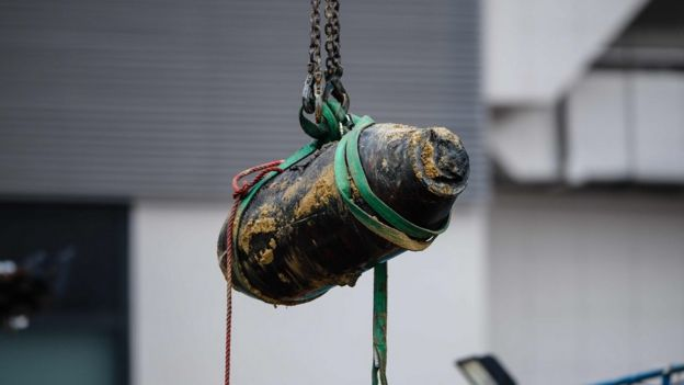 A defused US-made bomb dropped during World War II is lifted by crane