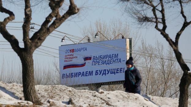 Una mujer pasa al lado de un cartel que anuncia las elecciones
