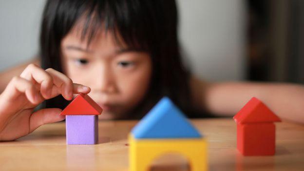 Menina construindo casinha de madeira