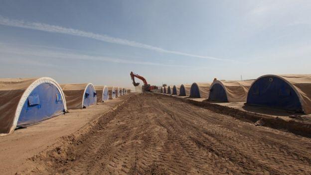 Workers prepare a tent camp west of the Kurdish regional capital Irbil, Iraq