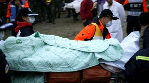 Rescuers transport a body on the second day of search and rescue operation from a collapsed building following a 6.4 magnitude earthquake struck on 06 February in Tainan City, southern Taiwan, 07 February 2016