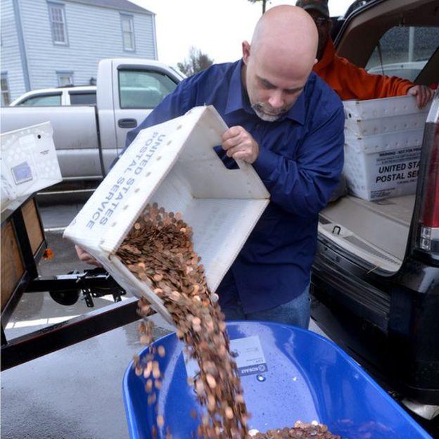 Nick Stafford pouring coins into a wheelbarrow (11 January 2017)