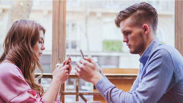 pareja usando celular.
