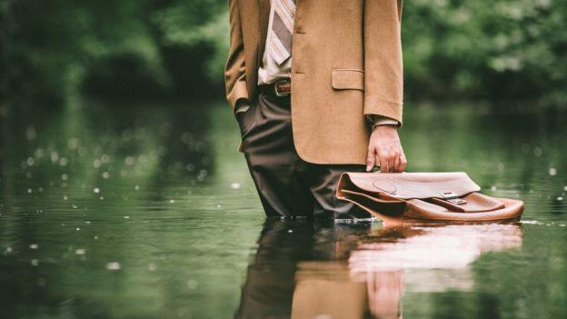 Homem de terno, gravata e maleta em meio a um lago