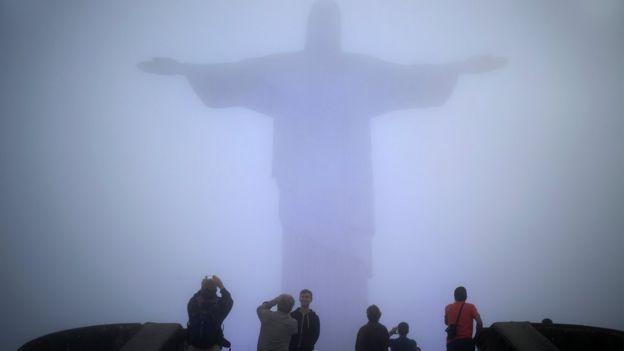Turistas fotografam Cristo Redentor sob névoa
