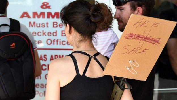 Mulher com cartaz anunciando promoção de rifles AR-15